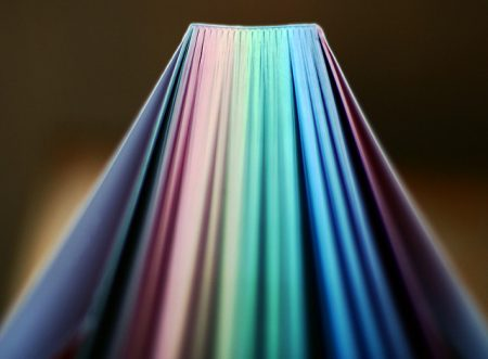 book with rainbow paged fanned out in soft light