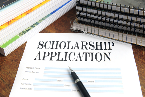 paper application for a scholarship lying on a table, with a pen on top