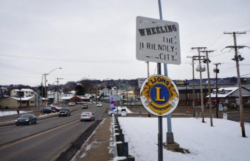 street sign - welcome to Wheeling - road with a few cars in background